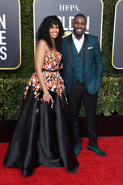 Sabrina Dhowr wearing the Jonatina sandal in black satin and carrying a black velvet clutch on the arm of partner Idris Elba in his assorted Greggo dress shoes